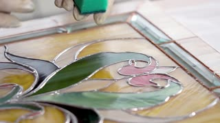 Close-up of masters hands are washing stained-glass. Panel is lying on a table, worker is rubbing a surface of product