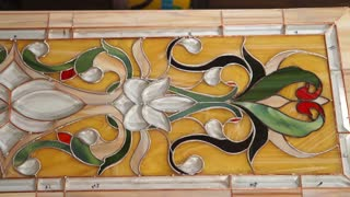 Close up shot of a beautiful finished stained glass lying on the table in a workshop. Decorations and patterns.
