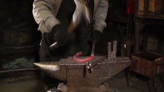 close up shot of a blacksmith's hands, a professional worker beats a hammer on the horseshoe, which was made of bent steel by several heated metal