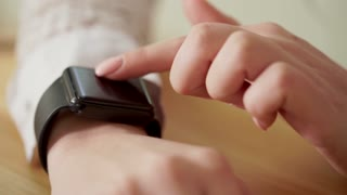 Close up shot of a business woman hands, who checks the news on a smart watch to be up to date with the latest news.