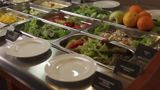 Close up shot of a cooked food and fresh vegetable in food trays in buffet. Different kind of food. Big choice.