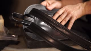 Close-up shot of a craftsman making black leather backpack for women. Handmade product