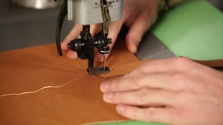 Close-up shot of a craftsman stitching leather strap with sewing machine. Making handmade notebook