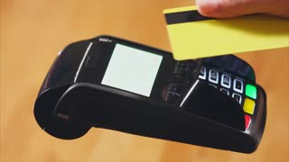Close-up shot of a customer paying in the store with a contactless bank card and entering a pin-code. NFC technology
