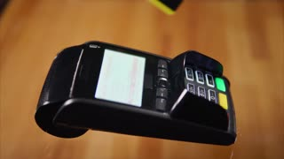 Close-up shot of a customer sliding credit card on bank terminal and entering a pin code. Noncash payments for goods and services