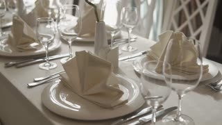 Close up shot of a decorated table with plates glasses and white napkins indoor. Clean cultery on the table.