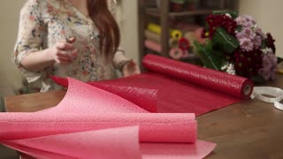 close up shot of a florist hand, a woman cuts off with a scissors a piece of red paper, then she wraps in it chrysanthemums that lie next to the table