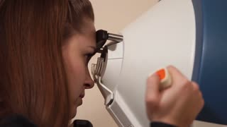 Close up shot of a girl getting her cornea of eye examined at ophthalmologist. Sitting and looking into special medical equipment.