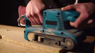 Close up shot of a handy man using wood polishing tool indoor. Polishing a piece of wood board.