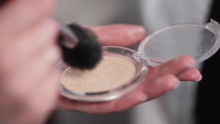 Close up shot of a make up artist getting powder on brush from a box. She is holding cosmetic powder.