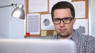 close up shot of a man in glasses who works behind a laptop in his office with diagrams on the wall. A person with poor eyesight spends a lot of time in front of the monitor using the Internet