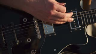 Close-up shot of a man plying solo guitar in music band. View to the hand plucking fingerboard