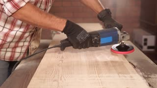close up shot of a man's hands, who works with an electric drill with a nozzle for polishing a wooden surface, a carpenter working in his workshop to fix and create furniture