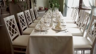 Close up shot of a nicely served table in restaurant. Decorated table with a clean plates glasses and white napkins.