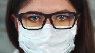 close up shot of a portrait of a young woman with glasses due to a bad look and a mask on her mouth and nose, the lady looks like a therapist's doctor or a nurse at a polyclinic