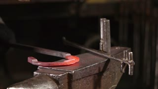 Close up shot of a professional smith working with a metal in a forge. Spark and pieces of metal popping off.