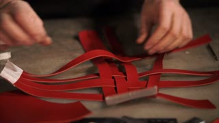 Close up shot of a skillful craftsman braiding leather stripes in a workshop. He is making brand new item.