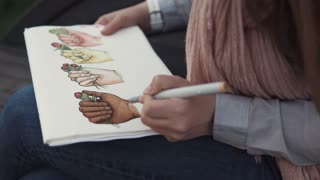 Close up shot of a talented woman drawing in a sketchbook with markers. Fantastic bright drawing of hands with flowers. Great art.