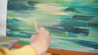 Close-up shot of a woman artist making brush strokes with oil on canvas. Impressionist painter working en plein air