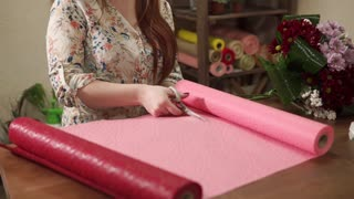 Close up shot of a woman cutting decorative paper on the table indoor. She is making a wrap for bouquet.