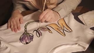 Close up shot of a woman drawing on a white sweatshirt indoor. Carefully lining the drawing with a brush. Bright work and lovely idea.