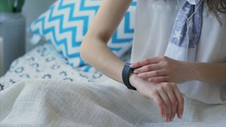 Close up shot of a woman holding hands, who immediately after waking up in the bed of a sleeping room checks incoming messages on a smart watch. A woman touching the gadget's screen.