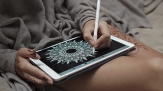 Close up shot of a woman sitting in bed drawing mandala on tablet using sylus. Beautiful art. Practicing.