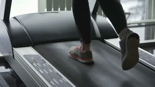 Close up shot of a woman who quickly walks along a treadmill uphill. Sportswoman of the program on the remote controls to better maintain muscle tone and fitness.
