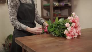 close up shot of a woman's hands, who makes a bouquet of flowers in a flower shop where she works, a lady ties a ribbon to green stems with leaves
