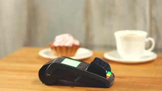 Close up shot of a woman's hands, who pays for desserts and coffee by applying a bank card to the terminal in a small cafe. The woman is buying sweetness