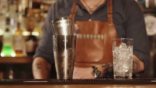 Close up shot of a working bartender using shakers. He is pouring drink from one to another.