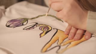 Close up shot of a young girl doing incredible drawing on a white sweatshirt. Using brush for coloring the painting. Cloth design.