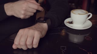 Close up shot of a young man's hand, which checks incoming mail on smart watch.