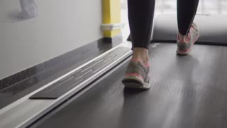 Close up shot of athlete's foot that follows the treadmill. A woman in a sneaker moves fast with her feet on a sports simulator, correct position of the foot helps improve the efficiency of exercises.