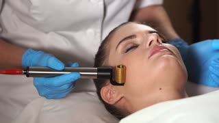 Close up shot of cosmetologist uses microneedle mesotherapy roller. Non-needle type of mesotherapy called mesoporation. Woman getting facial rejuvenation and lifting procedure.