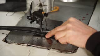 Close-up shot of craftsman working with sewing machine. He stitching black leather handle for women handbag