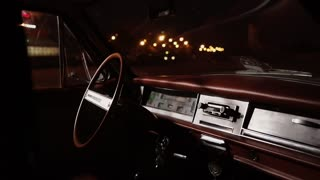 Close up shot of dashboard of a luxury vintage vehicle. City lights outside the car shining bright.