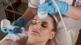 Close up shot of face skin care. Woman gets procedure in the beauty salon. Anti-aging RF-therapy, rejuvenation and lifting procedure.