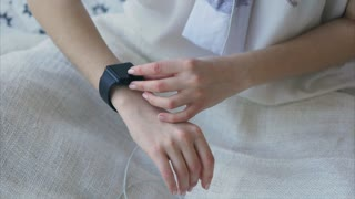 Close up shot of female hand, who uses a gift from parents - a smart watch. The girl checks her pulse on a black touch screen in order to familiarize herself with the gadget.