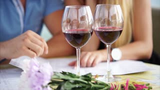 Close up shot of glass glasses of red wine, in the background sit a man and woman and view the menu, a couple in love is in a restaurant and choose the main dish