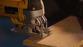 Close up shot of handy man working with a wood board indoor under the light. He is cutting off a small part of wood board with a saw.