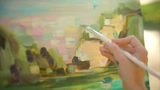 Close-up shot of impressionist painter making final brush strokes during plein air painting