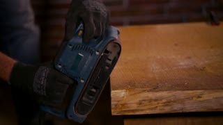 Close up shot of male carpenter rounding the edges of a wooden table with sanding machine. Giving fresh look to the wood.
