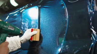 Close up shot of man applying vinyl film while tuning expensive blue car.