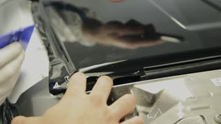 Close up shot of man cutting vinyl film while tuning car