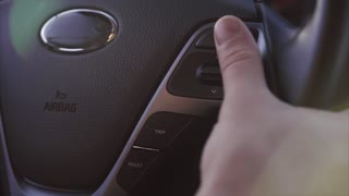 Close up shot of man's hand changing configuration settings on steering wheel.
