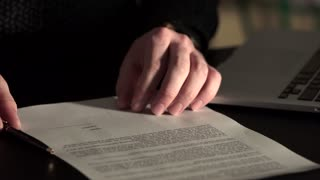 Close up shot of man's hands, who leaves signature on the agreement.