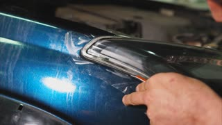 Close up shot of master cutting vinyl film by special knife. Expert makes more accurate the pattern for further bonding film on the headlights.