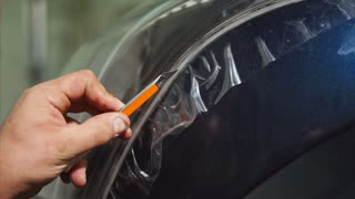 Close up shot of master cutting vinyl film by special knife on the blue car. Expert makes more accurate the pattern for further bonding film on the headlights.