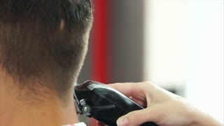 Close up shot of the barber's hands, who cuts the hair of the man on his head, the hair stylist uses an electric hair machine to change the length of the hair behind